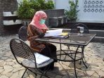 Menjalani Isolasi Mandiri, Gubernur Jatim, Khofiffah Indar Parawansa memeriksa surat dengan berjemur matahari